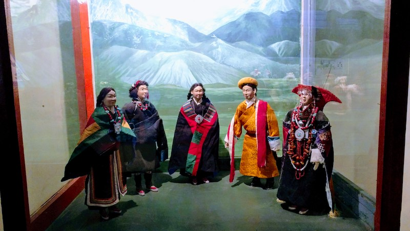 Costumes worn by the people of Ngari in Tibet. Behind is the Mount Kailash, the most celebrated mountain in Tibet.
