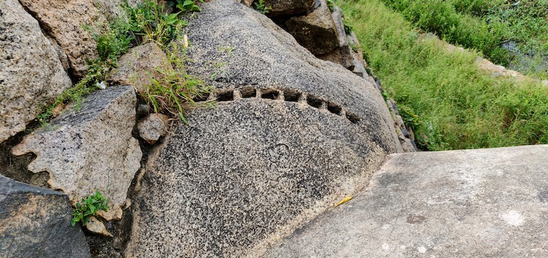 A series of small holes seen in the boulder