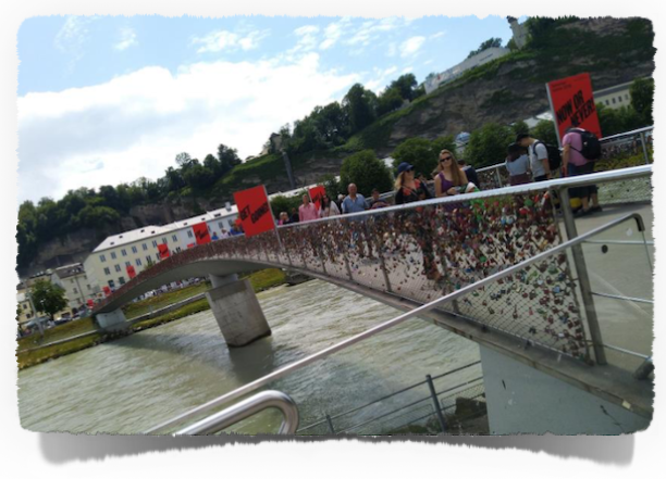 The footbridge across the Salzach River leading to the Old Town. It is a popular custom for tourists (couples) to secure a padlock to the foot bridge written with their names as a romantic gesture, and to throw the key into the river (to seal their love) which is a tradition originated in Hungary.