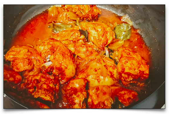 The chicken stewing in the kadai