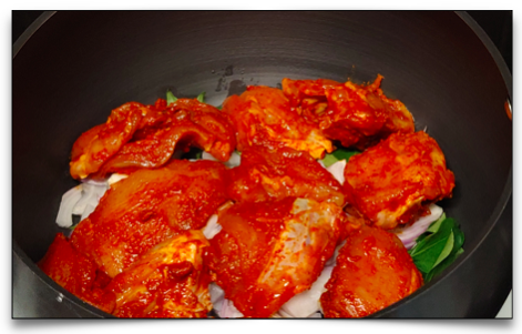 In the kadai - coconut oil, sliced onion, curry leaves and the marinated chicken pieces