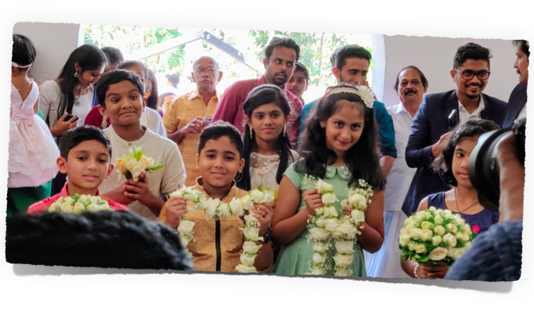 Kids waiting to greet the couple with floral bouquets and garlands after the ceremony