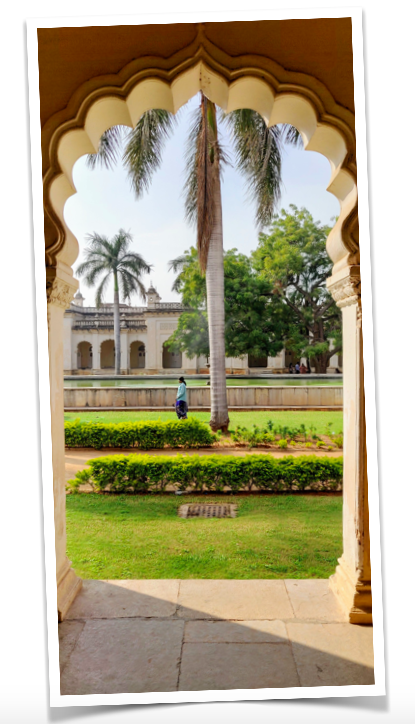 An arch framing the garden and pool and the opposite building running as mirror images at the Chowmohalla Palace, Hyderabad
