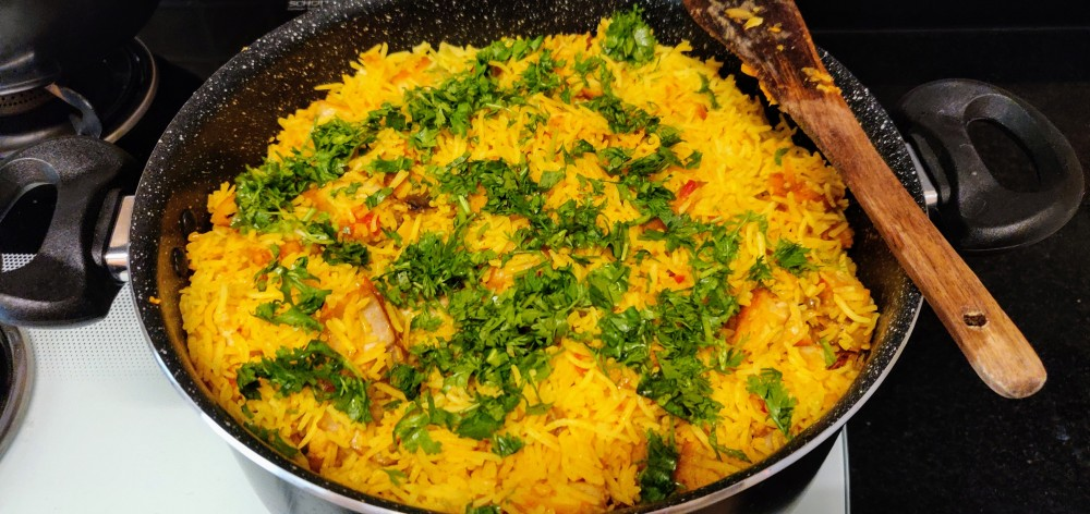 A generous sprinkle of chopped coriander leaves over the top of the biryani